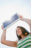 Mixed race woman holding solar panel