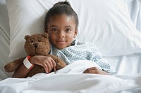 Mixed race girl in hospital bed with teddy bear