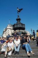 People sitting in front of Eros Statue, London, England, UK