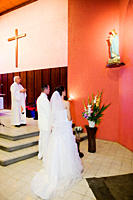 Bride and groom praying in front of the virgin mary in their ceremonial dress