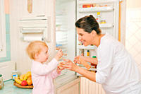 Mother and daughter in the kitchen giving the recently picked yoghourt a try in front of the open fridge