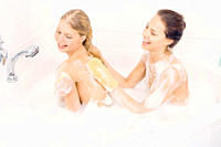 Two young adobable girls enjoy taking a bath together in the bathtub