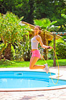 Young woman jump roping in the garden by the pool on a sunny day