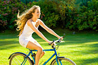 Young woman enjoys to ride her bike on a beautiful sunny summers day