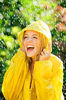 Young woman wearing a raincoat enjoying the slight rain shower during a warm summers day