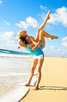 Two young women working out on a beach giving each other a piggyback ride