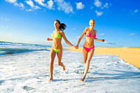 Two women dressed in bikinis jogging along the coastal line and holding their hands