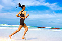 Young woman jogging through the water at the beach