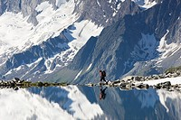 Hiker reflected in the Friesenbergsee lake, Zillertal Alps, Tyrol, Austria, Europe