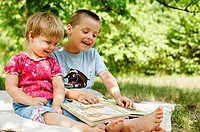 Children reading book in the garden