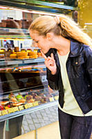 Young woman shopping and looking through the display window of a bakery