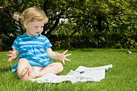 Child sitting on grass and looking at magazines.