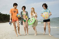 Four friends walking on the beach with sport and beach accessories .