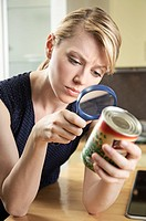 Young woman looking at a label on a canned green peas using magnifying glass in the kitchen.