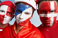 Football fans with coloured faces.