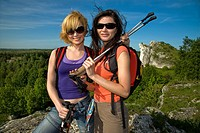 Two women holding ski sticks standing on a hill.