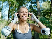 Young woman listening to the music after training.
