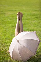Young woman lying in grass, behind an umbrella