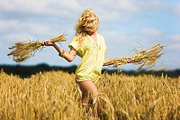 Young woman holding wheat in a field (thumbnail)