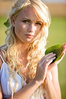 Young woman holding green leaves (thumbnail)