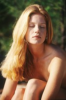 Portrait of a young woman sitting outdoors, sunbathing