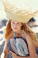 Young woman crouching, sunhat, seaside