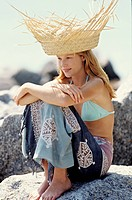 Young woman sitting on a rock, sunhat, outdoors
