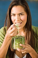 Portrait of a woman eating bean sprouts