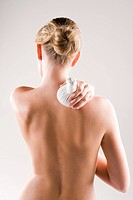 Woman massaging her shoulder with a herbal pack