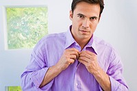 Portrait of a man buttoning shirt