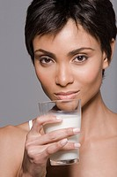 Portrait of a woman holding a glass of milk