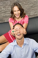 Woman covering a man's eyes from behind