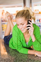 Woman lying on the kitchen counter and talking on a mobile phone (thumbnail)