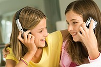 Girl talking on a mobile phone and her sister listening to headphones