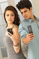 Couple holding mobile phones (thumbnail)