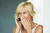 Woman talking on a mobile phone and surprised