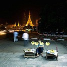 Teenage boy selling bananas with a pagoda lit up in the background, Yangon, Myanmar