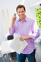 Man talking on a mobile phone and holding a newspaper