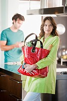 Woman holding a shopping bag in the kitchen