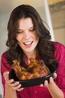 Woman holding a tray of roasted chicken