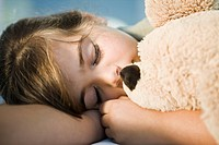 Close_up of a girl sleeping with a teddy bear