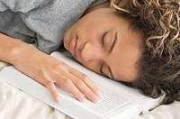 Girl sleeping with her face down on a book