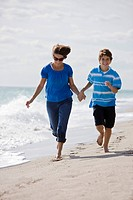 Woman running on the beach with her grandson