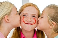 Close-up of two girls kissing their friend (thumbnail)