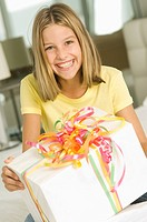 Girl holding a birthday present and smiling