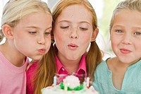Close_up of three girls blowing out candles on a birthday cake