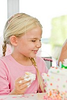 Close_up of a girl eating birthday cake