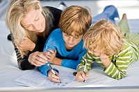 Woman helping her sons in their homework