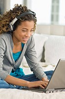Girl working on a laptop and listening to headphones