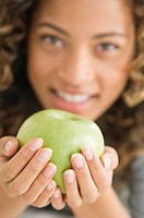Portrait of a girl holding a green apple and smiling (thumbnail)